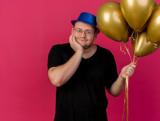 Il compiaciuto uomo slavo adulto in occhiali ottici che indossa un cappello da festa blu mette la mano sul mento e tiene palloncini di elio