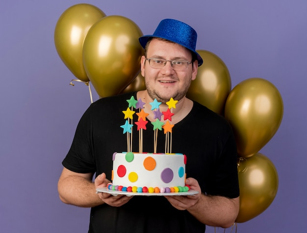 Pleased adult slavic man in optical glasses wearing blue party hat stands in front of helium balloons holds birthday cake