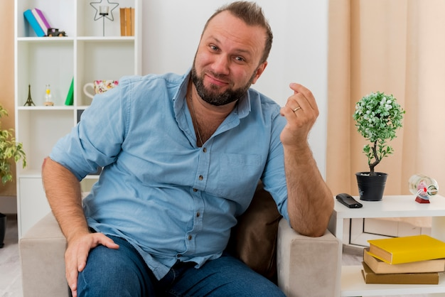 Pleased adult slavic man sits on armchair gesturing money hand sign inside the living room