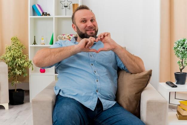 満足している大人のスラブ人は、リビングルーム内のハートの手振りを身振りで示すアームチェアに座っています