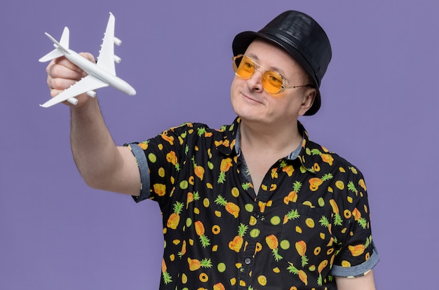 Pleased adult slavic man with black top hat wearing sunglasses holding and looking at plane model