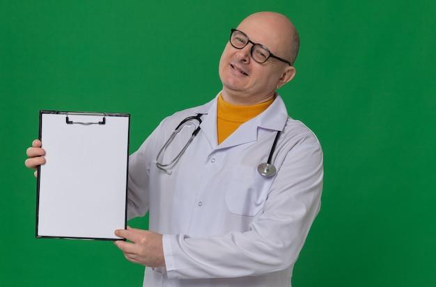 クリップボードを保持している聴診器で医者の制服を着た光学メガネで満足している大人のスラブ人