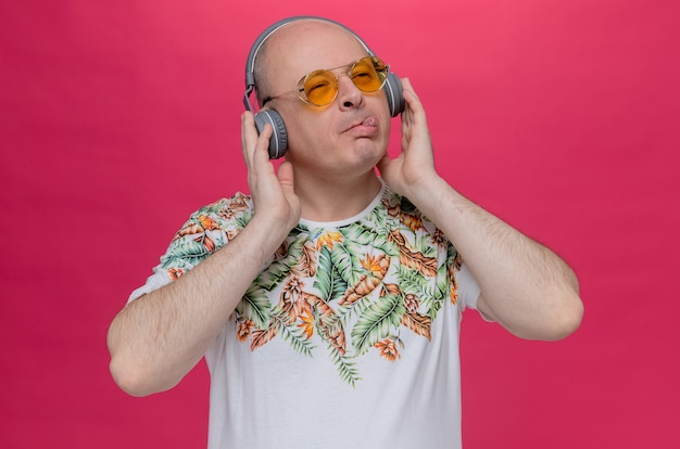 Pleased adult slavic man with sunglasses and on headphones stucks out his tongue and looks at side
