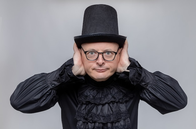 Pleased adult slavic man with top hat and optical glasses in black gothic shirt putting hands on his ears and looking at front