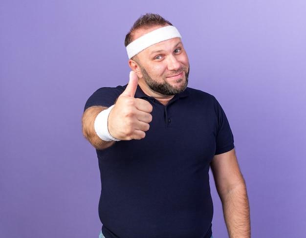 머리띠와 팔찌를 입고 기쁘게 성인 슬라브 스포티 한 남자는 복사 공간이 보라색 벽에 고립 엄지 손가락