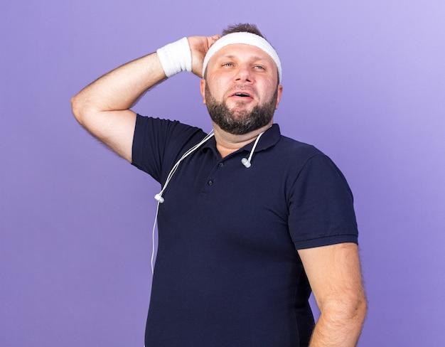 Uomo sportivo slavo adulto soddisfatto con le cuffie intorno al collo che indossa fascia e braccialetti mettendo la mano sulla testa e guardando il lato isolato sulla parete viola con spazio di copia