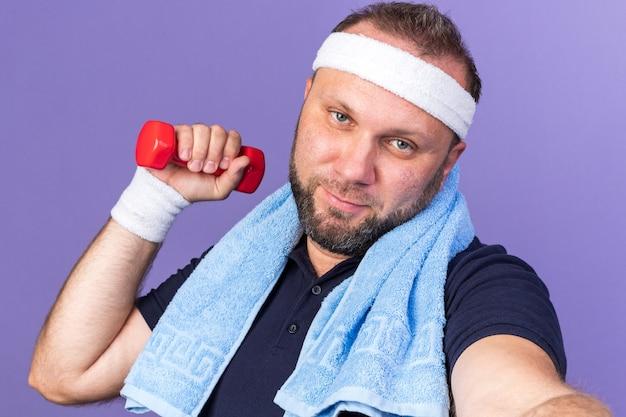Довольный взрослый славянский спортивный мужчина с полотенцем на шее, с головной повязкой и браслетами, держащий гантели, изолированные на фиолетовой стене с копией пространства