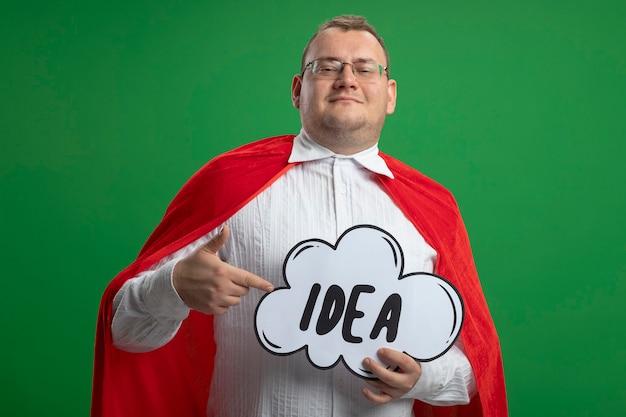 緑の壁に分離されたアイデアの泡を保持し、指している眼鏡をかけて赤いマントで喜んで大人のスラブのスーパーヒーローの男