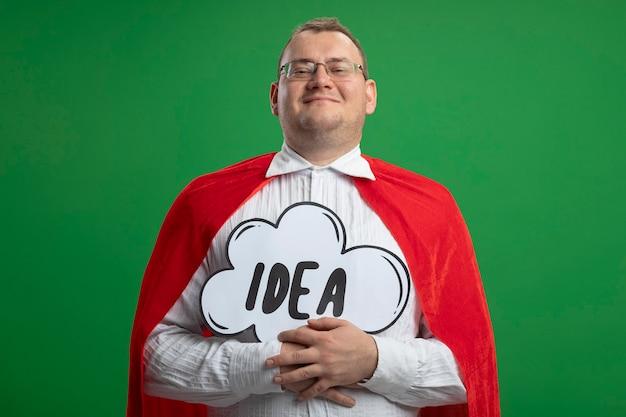Довольный взрослый славянский супергерой в красной накидке в очках, держащий пузырь идеи, смотрящий в камеру, изолированную на зеленом фоне