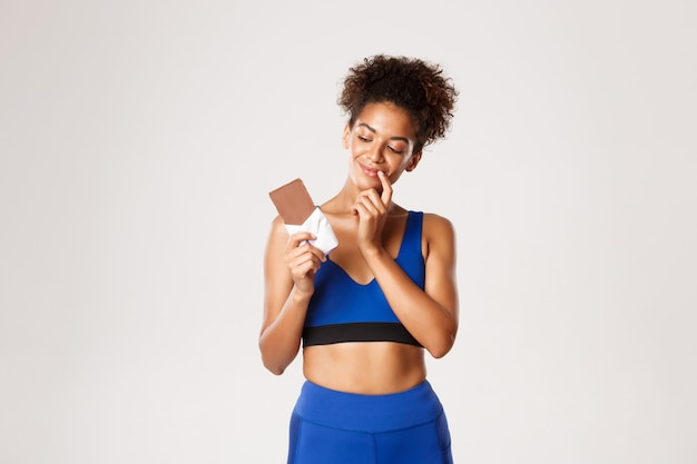 Pleased african-american fitness woman in blue sport costume, looking at chocolate bar with tempted