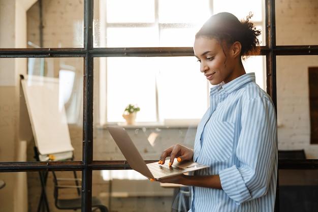 Довольная афро-американская женщина улыбается и печатает на ноутбуке, стоя в современном офисе