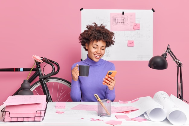 Pleased african american woman using smartphone, drinks coffee, dressed in casual jumper poses at desktop with papers around works on future engineer project