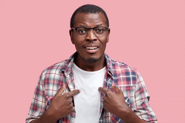 Pleased african american young man wears white t shirt and checkered shirt, indicates at clothing with blank space