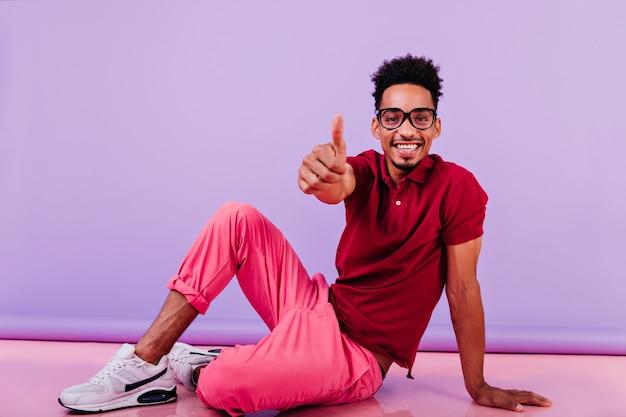 親指を立てて床に座っているアフリカの男性モデルを喜ばせます。ポジティブな感情を表現する眼鏡をかけた明るい黒人の男。