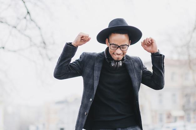 手を上げてポーズをとる優しい笑顔でアフリカ人を喜ばせます。幸せな黒人男性モデルの屋外の肖像画は、流行のスーツを着ています。