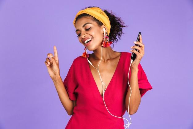 Довольная африканская женщина в платье и наушниках слушает музыку с закрытыми глазами над фиолетовой стеной
