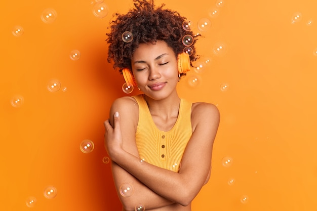 Pleased afro american woman embraces herself stands with bare shoulders closes eyes in satisfaction listens music via stereo headphones poses against orange studio wall with soap bubbles around