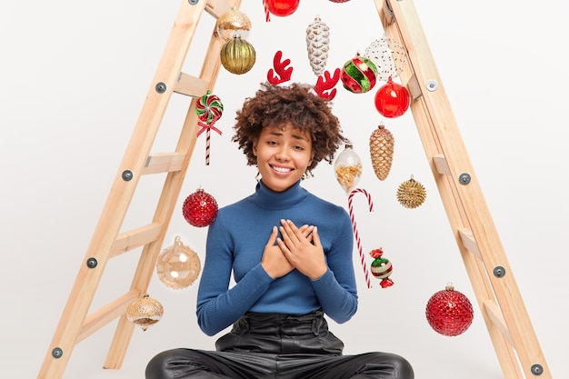 곱슬 머리를 가진 기쁘게 아프리카 계 미국인 여자는 크리스마스 포즈에받은 선물로 감사 제스처를 만집니다.