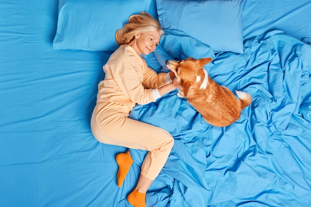 Pleased aged european woman in nightwear plays with favorite pet at home in bedroom lying together in bed enjoy good day. middle aged female expresses love and care to dog as member of family