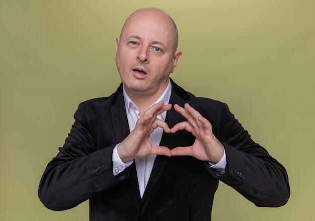 Довольный и счастливый лысый мужчина средних лет в костюме смотрит вперед, делая сердечный жест с пальцами, стоящими над зеленой стеной