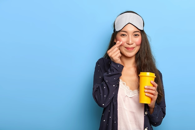 Pleased asain dark haired woman makes korean like gesture, dressed in pyjamas and sleep mask, holds yellow takeout coffee cup