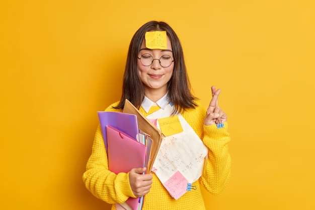 Pleased asain female student believes in good luck at exam stands with eyes closed and fingers crossed believes dreams come true stuck with papers holds folders.
