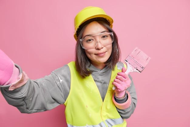 만족 한 아시아 건축업자가 보호용 하드 모자를 쓰고 투명 안경 작업복을 들고 페인트 브러시를 들고 아파트 벽을 새로 장식 한 후 셀카를 찍습니다.