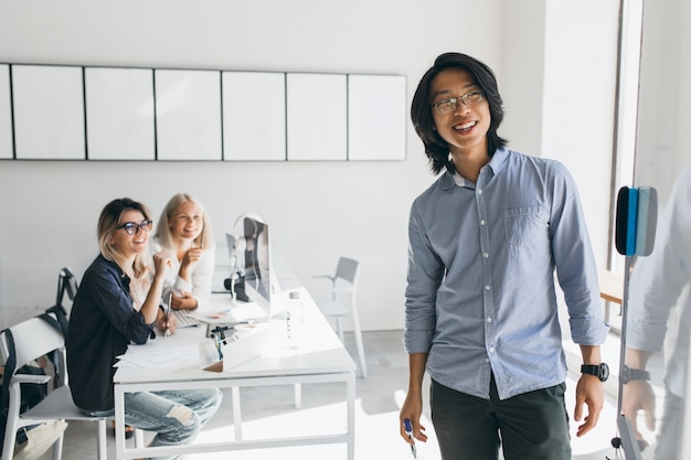 Доволен азиатский бизнесмен, глядя на флипчарт с улыбкой, стоя в конференц-зале. очаровательные белокурые студентки с ноутбуками наблюдают за молодым учителем, пишущим на борту.