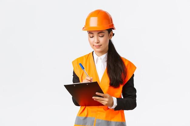 クリップボードにメモを取っているアジアの女性建設エンジニアの建築家が何かを書き留めて喜んでいます...