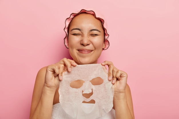Pleased asian female holds facial sheet mask, going to apply on face, gets pleasure from beauty treatments, keeps eyes closed