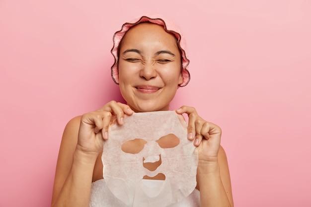 満足しているアジアの女性は、顔のシートマスクを保持し、顔に適用し、美容トリートメントから喜びを得て、目を閉じたままにします