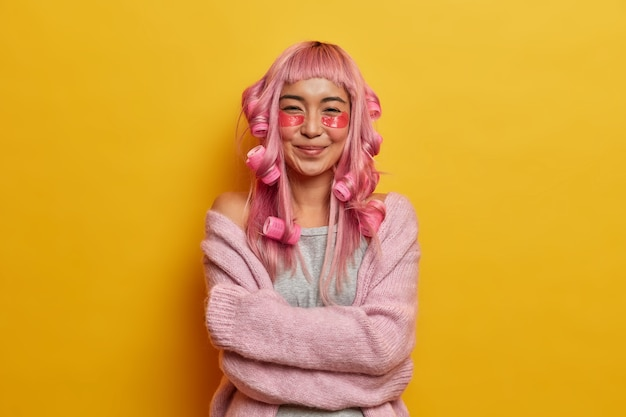 Pleased asian girl feels comfort in woolen jumper, embraces herself and smiles gently, has pink hair, makes hairstyle with curlers, applies beauty pads