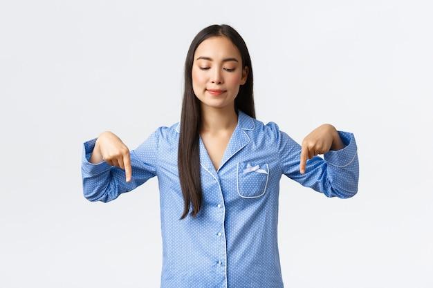 파란색 잠옷을 입은 아시아 소녀가 유혹적인 것을 보고 만족하고 사려 깊은 미소를 지으며 제품이 있는 아래쪽 배너를 아래로 가리키며 좋은 것을 찾았습니다. 흰색 배경