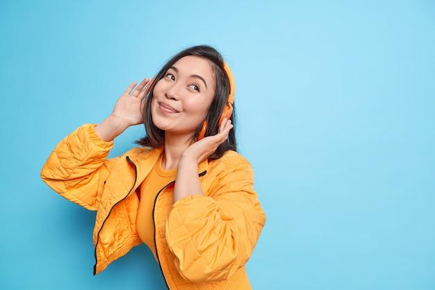 Довольная азиатская девушка смотрит со счастливым мечтательным выражением лица, слушая тексты песен из своего плейлиста, в беспроводных стереонаушниках модели оранжевой куртки на фоне синей стены свободное пространство справа