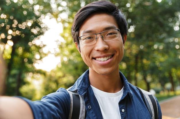自撮り写真を撮ったり、屋外でカメラを見たりする眼鏡をかけたアジア人男性学生