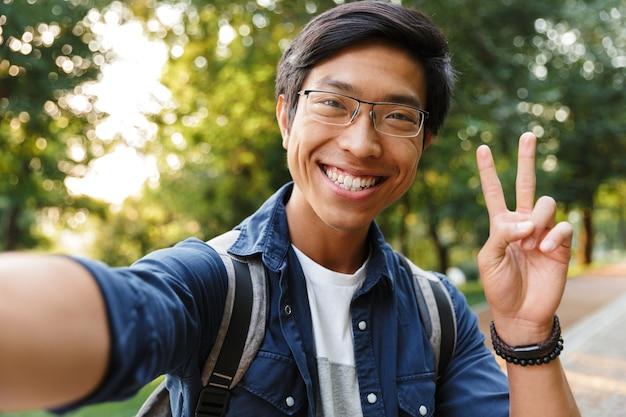 屋外でカメラを見ながら自分撮りをし、平和のジェスチャーを示す眼鏡で喜んでいるアジアの男子生徒