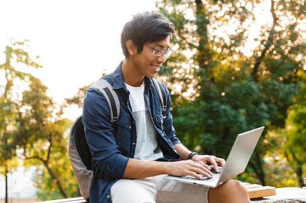 公園のベンチに座っている間ラップトップコンピューターを使用して眼鏡でアジアの男子学生を喜ばせる