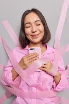 Pleased asian woman holds mobile phone uses modern application satisfied to receive message from boyfriend chats in social networks closes eyes from pleasure wrapped with tapes wears pink shirt