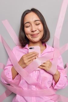 Довольная азиатская женщина держит мобильный телефон, использует современное приложение, довольная, чтобы получать сообщения из чатов парня в социальных сетях, закрывает глаза от удовольствия, завернутая в ленты, носит розовую рубашку