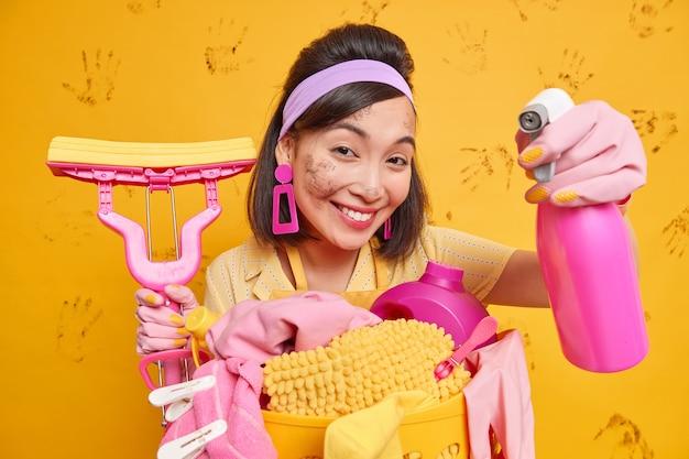 満足しているアジアの女性ハウスキーパーはヘッドバンドを着用し、イヤリングは多くの責任を負っています部屋を掃除し、洗剤を保持し、洗濯をするのに忙しいモップは幸せなフレンドリーな表現をしています