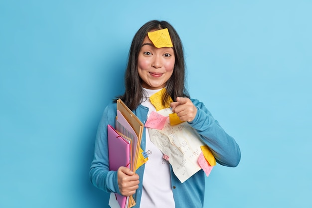 Pleased asian woman office worker with pleased expression holds a folder and indicates directly at camera