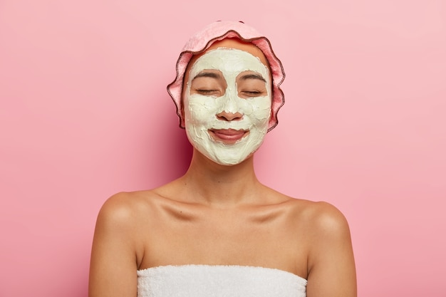 Pleased asian woman wears clay purifying organic mask on face, has beauty procedures in spa salon, wears rosy soft protective showercap