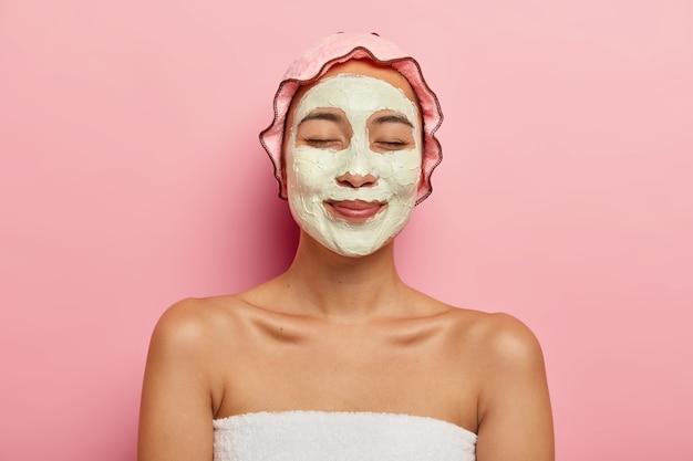 기쁘게 아시아 여자는 얼굴에 점토 정화 유기 마스크를 착용하고, 스파 살롱에서 미용 절차를 가지고, 장밋빛 부드러운 보호 샤워 캡을 착용