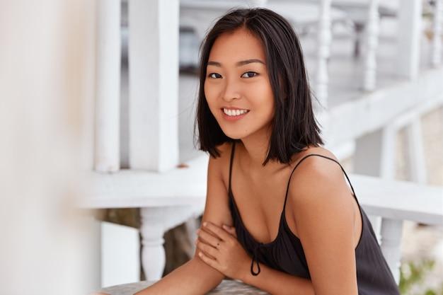넓은 미소를 지닌 기뻐하는 아시아 여성은 단발 머리 헤어 스타일을하고, 캐주얼 한 옷을 입고, 카페 테이블에 앉아, 레크리에이션 시간을 즐깁니다. 아름다운 일본 여성은 레스토랑에 혼자 달려있다