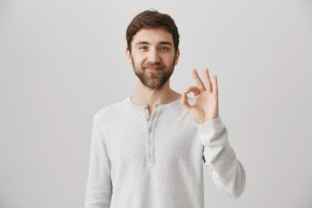 Довольный привлекательный бородатый мужчина показывает хорошо, подписывается в утверждении