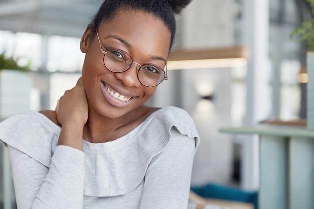 魅力的な暗い肌の女性モデルは眼鏡をかけ、輝く笑顔を持ち、仕事を終えてうれしく、休憩し、オフィスのインテリアに対してポーズをとります。