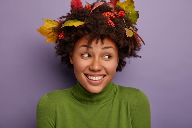 곱슬 머리를 가진 기쁘게 매력적인 아가씨, 옆으로 보이며, 넓은 미소를 지으며, 기분이 좋고, 터틀넥을 입고, 연인과 즐거운 시간을 보내고, 보라색에 고립되어 있습니다.