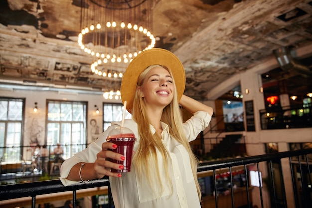 Pleased attractive long haired blonde lady standing over restaurant interior, leaning on iron railing and looking ahead with happy wide smile, holding hand on her wide brown hat