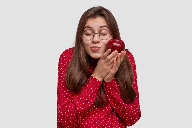 Piacevole donna attraente con i capelli scuri, tiene la mela rossa vicino alla guancia, chiude gli occhi, prova piacere, indossa occhiali rotondi