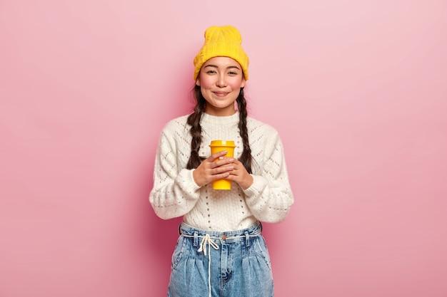 ひだを持った魅力的な女性は、身なりがよく、テイクアウトカップからコーヒーを飲むのが好きで、陽気な表情をしていて、ピンクの壁にポーズをとっています。